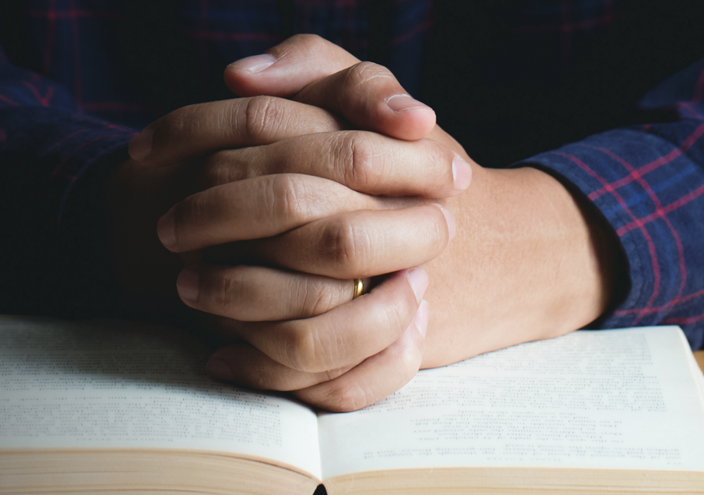Person praying with the bible